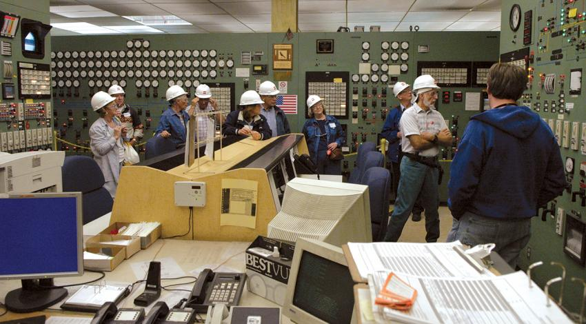 A group tours a room in a power plant.