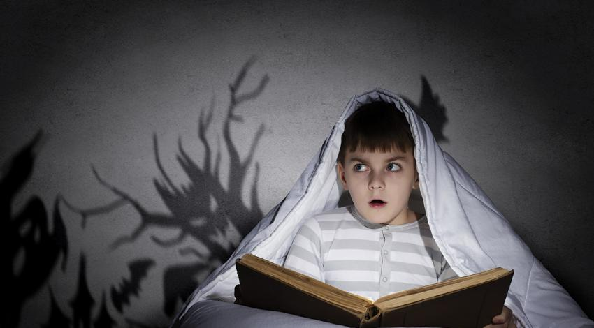 A boy reads under a blanket while scary shadows surround him.