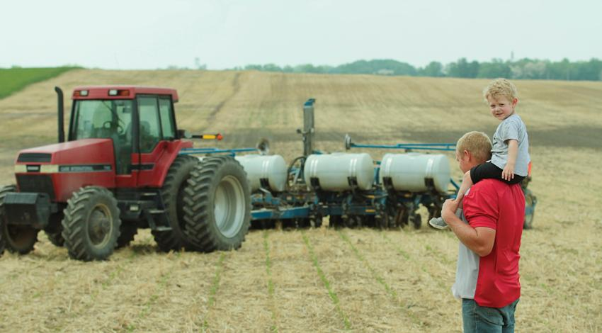Casey Longshore and his son, Landen, stand in a field beside a tractor.
