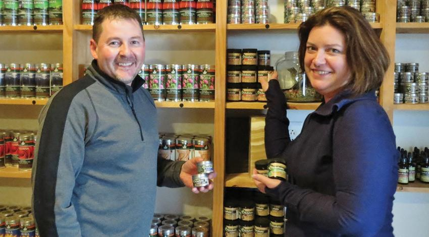 Dawn and Carson Combs pose for a figure alongside jars of products.