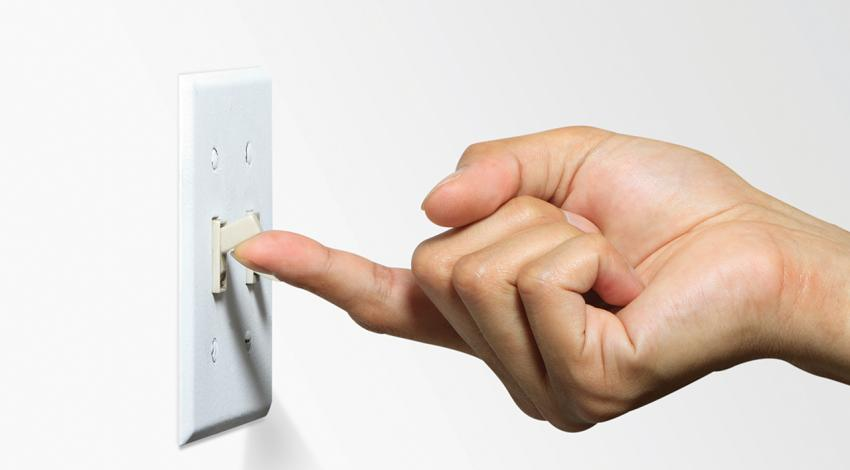 A hand flips on a light switch.
